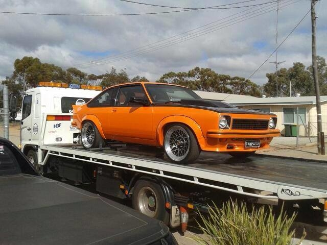 Orange and black car on a tilt tray truck