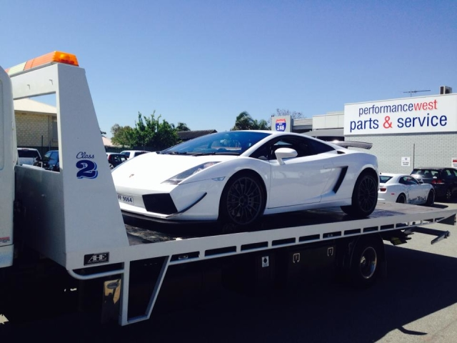 white Lamborghini towed by a tilt tray truck
