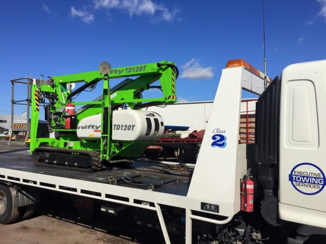 green cherry picker on a tilt tray in Perth