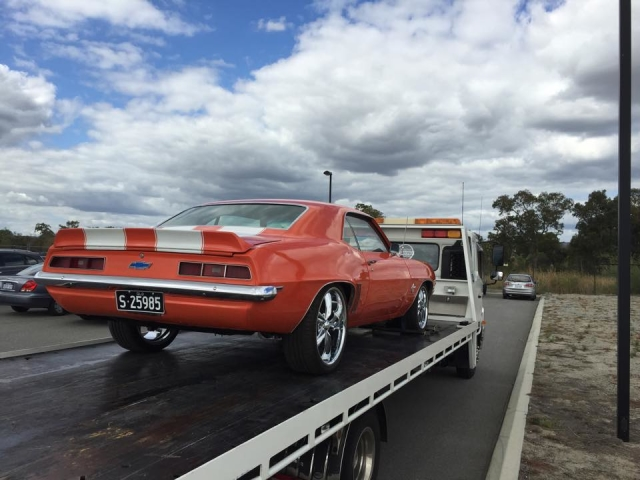 orange corvette being towed in Perth by a tilt tray