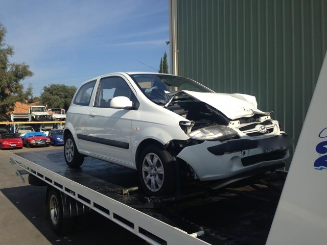 crashed white Hyundai on a tilt tray