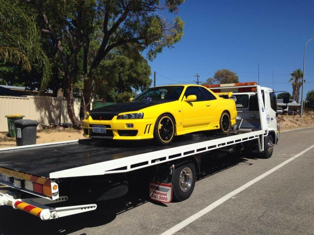 yellow and black performance car towed on a tilt tray