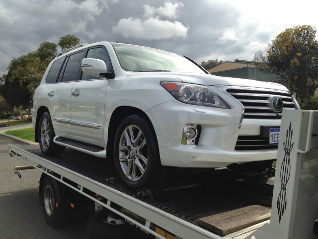 white Lexus on the back of a tilt tray transport