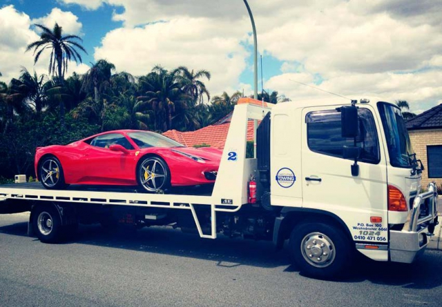 Executive Towing Services transporting a Ferrari on a tilt tray truck