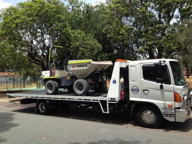 tilt tray truck transporting a small dumper